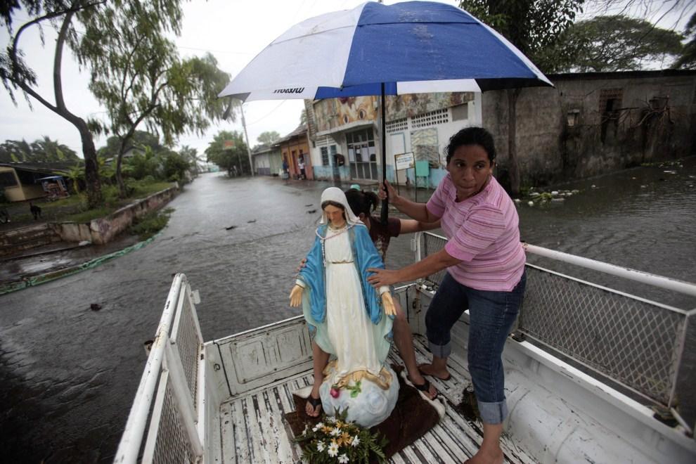 6. NIKARAGUA, Managua, 21 października 2011: Kobieta chroni przed deszczem figurę wywiezioną z zalanego kościoła w Managui. AFP PHOTO/ MAYERLING GARCIA