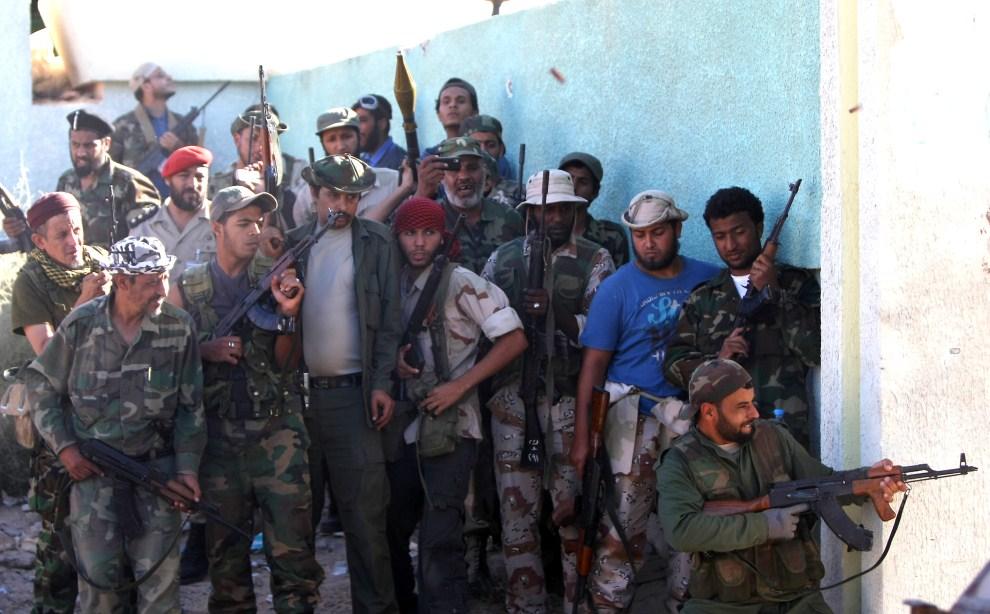 6. LIBIA, Syrta, 12 października 2011: Członkowie NTC przyglądają się strzelającemu bojownikowi. AFP PHOTO/AHMED AL-RUBAYE