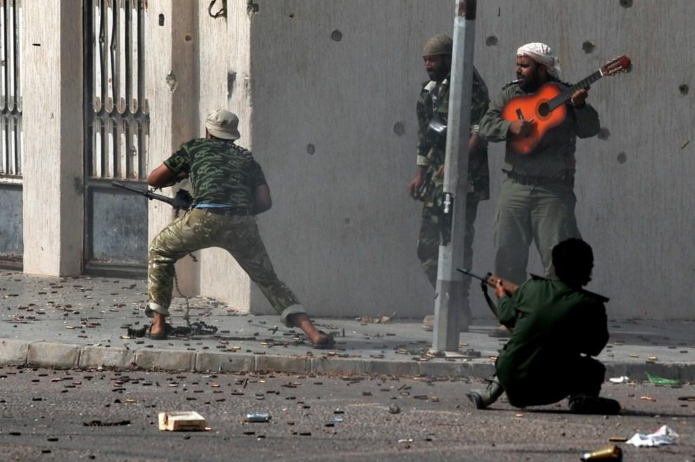 7. LIBIA, Syrta, 10 października 2011: Wymiana ognia na ulicy w centrum Syrty. AFP PHOTO / ARIS MESSINIS