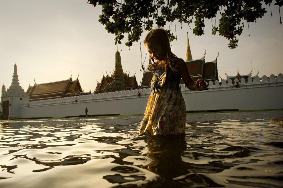 8. TAJLANDIA, Bangkok, 26 października 2011: Dziewczynka brodząca w wodzie przed Wielkim Pałacem Królewskim. AFP PHOTO / Nicolas ASFOURI