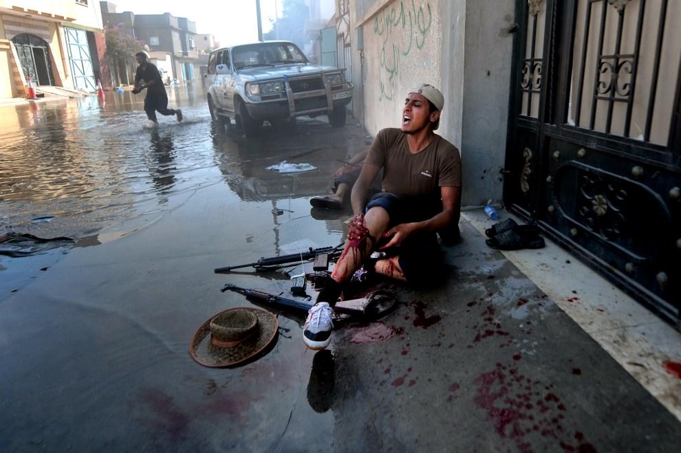8. LIBIA, Syrta, 12 października 2011: Bojownik NTC ranny w trakcie walki. AFP PHOTO / ARIS MESSINIS