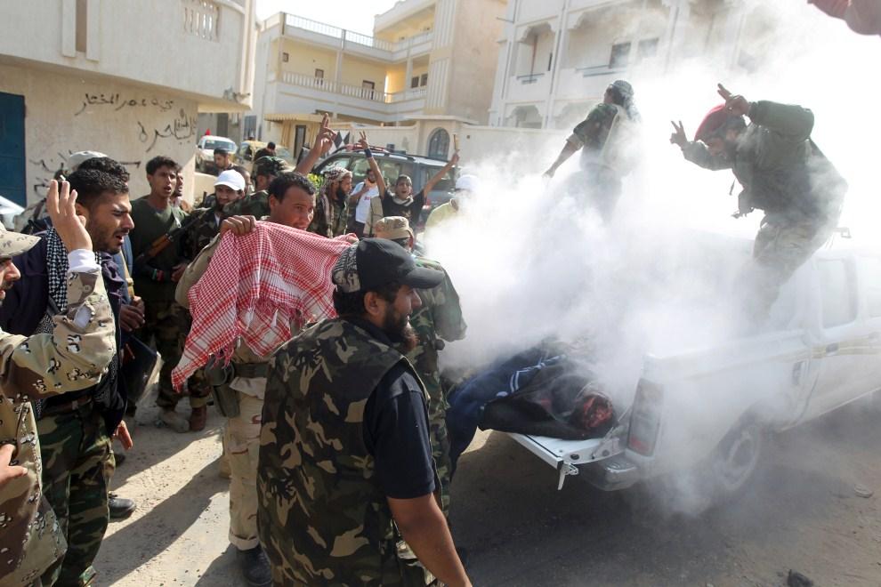 9. LIBIA, Syrta, 18 października 2011: Bojownicy NTC niosą ciało zabitego towarzysza. AFP PHOTO/AHMAD AL-RUBAYE