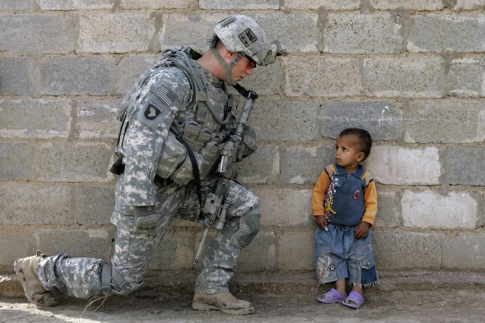 13. IRAK, Ad-Diwanijja, 2 maja 2008: Chłopiec przygląda się żołnierzowi patrolującemu ulicę w Bagdadzie. AFP PHOTO/MAURICIO LIMA