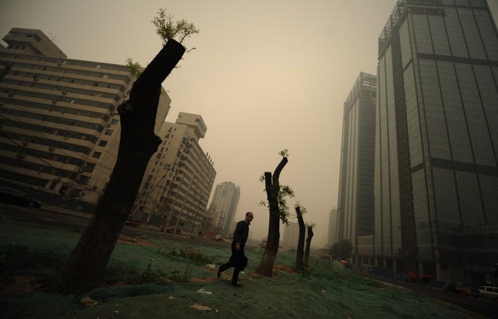 14. CHINY, Pekin, 1 listopada 2011: Mężczyzna na ulicy w centrum miasta, które spowił smog. AFP PHOTO/Peter PARKS