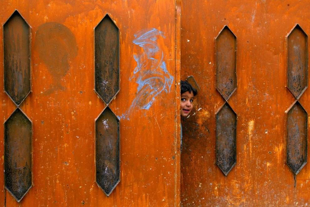 14. IRAK, Mosul, 4 lutego 2005: Chłopiec wygląda na ulicę przez bramę. AFP PHOTO/MAURICIO LIMA