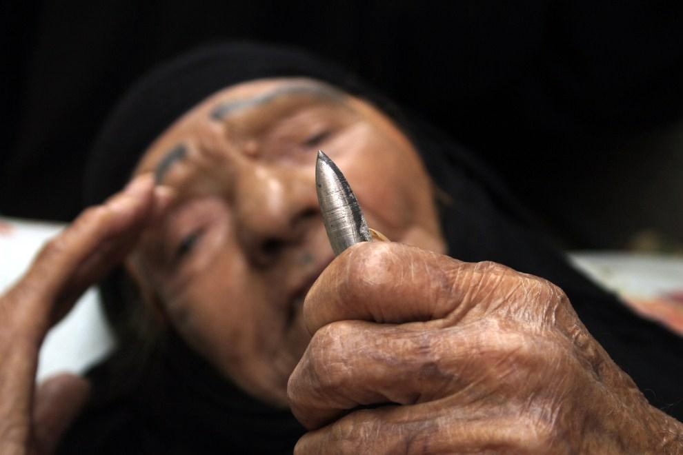 17. IRAK, Bagdad, 10 lipca 2007: Kobieta przygląda się pociskowi, który miał wpaść do jej sypialni podczas akcji wojsk amerykańskich. AFP PHOTO/WISSAM AL-OKAILI