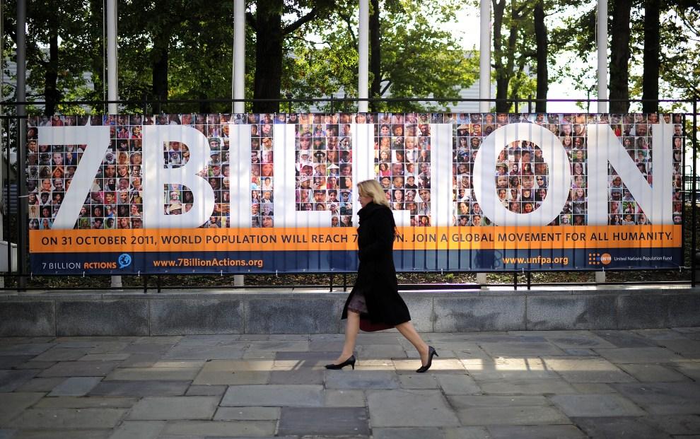 17. USA, Nowy Jork, 31 października 2011: Kobieta na tle plakatu informującego o narodzinach 7-miliardowego obywatela świata. AFP PHOTO/Emmanuel Dunand