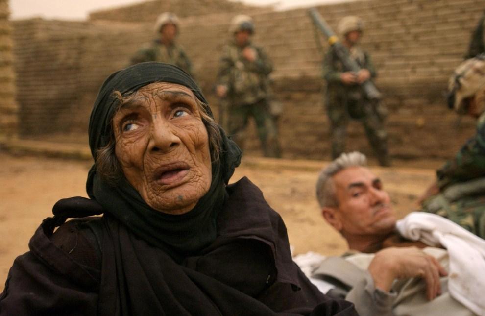 18. IRAK, Nasirijja, 27 marca 2003: Marines ewakuują rannych podczas strzelaniny niewidomą kobietę i mężczyznę. AFP PHOTO/Eric FEFERBERG