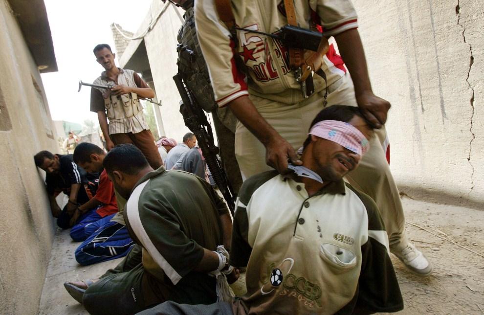 20. IRAK, Hawra Haajab, 6 września 2007: Ochotnik z oddziału walczącego po stronie USA przykłada nóż do gardła mężczyzny podejrzewanego o współpracę z Al-Kaidą. AFP PHOTO/DAVID FURST