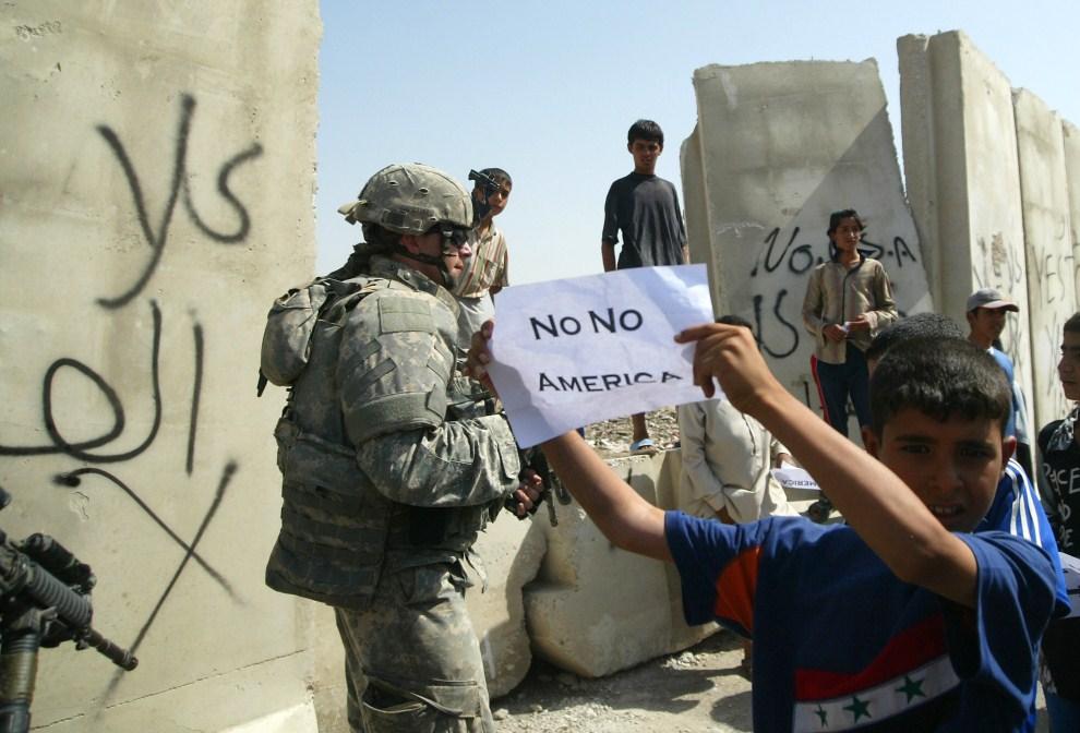 31. IRAK, Bagdad, 12 września 2007: Irakijczycy protestują przeciw budowie muru (w tle) oddzielającego  dzielnice Bagdadu. AFP PHOTO/ALI YUSSEF