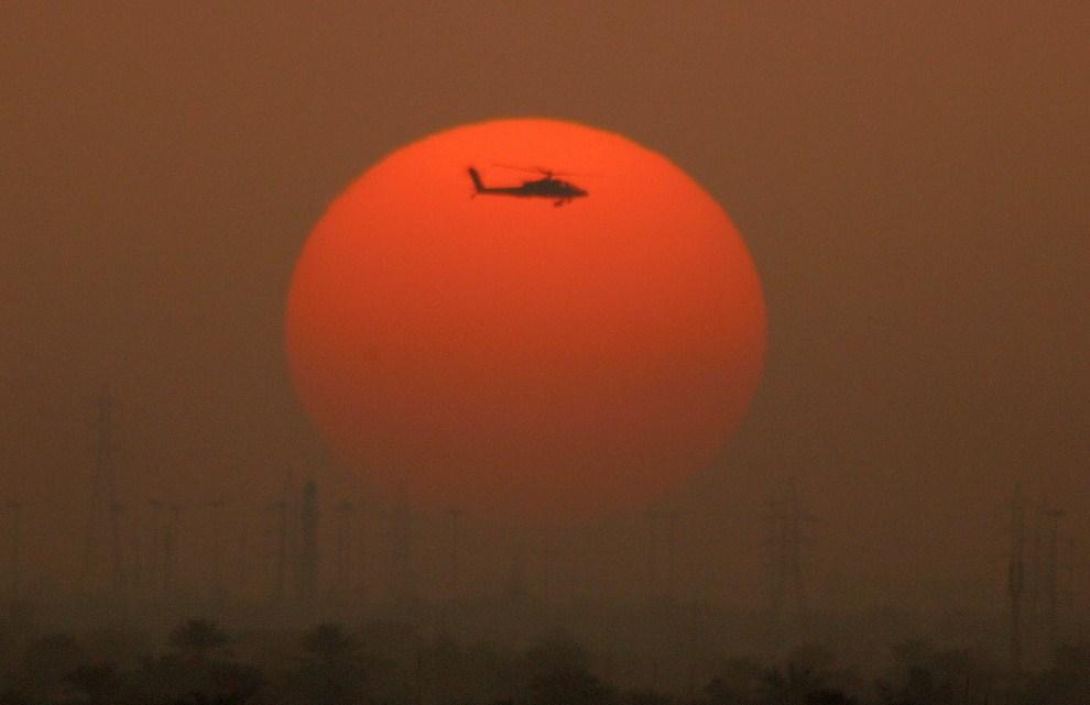35. IRAK, Bagdad, 21 marca 2011: Amerykański Apache nad Bagdadem na tle zachodzącego słońca. AFP PHOTO/PATRICK BAZ