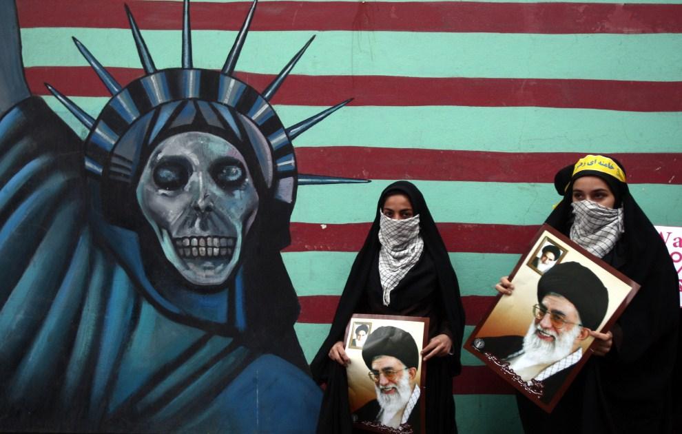 5. IRAN, Tehran, 4 listopada 2011: Iranki z wizerunkami Ajatollaha Chameneiego przed budynkiem byłej ambasady USA w Teheranie. AFP PHOTO/ATTA KENARE