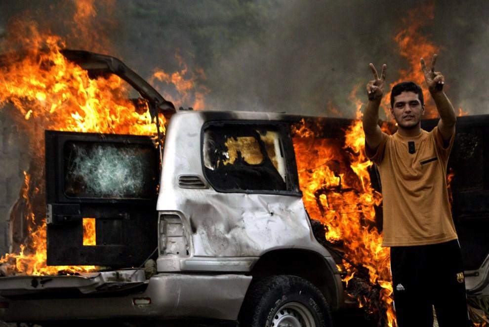 8. IRAK, Basra, 16 października 2006: Irakijczyk na tle pojazdu zniszczonego przez eksplozję. AFP PHOTO/ESSAM AL-SUDANI