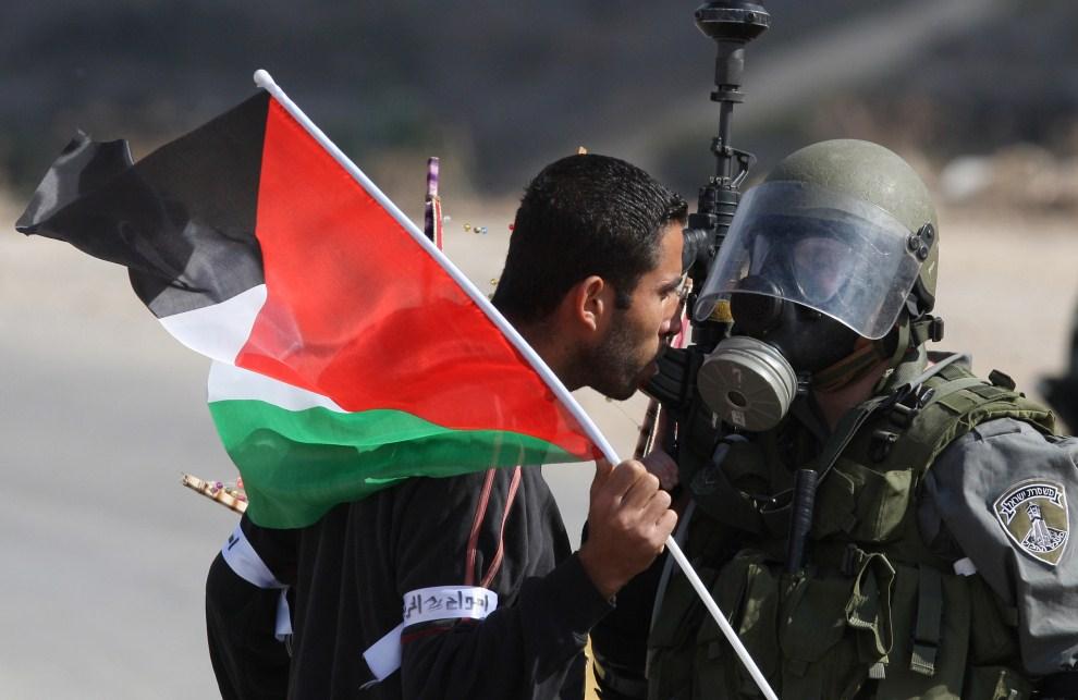8. ZACHODNI BRZEG, Nabi Salih, 4 listopada 2011: Palestyńczyk staje twarzą w twarz z izraelskim żołnierzem. AFP PHOTO/ABBAS MOMANI