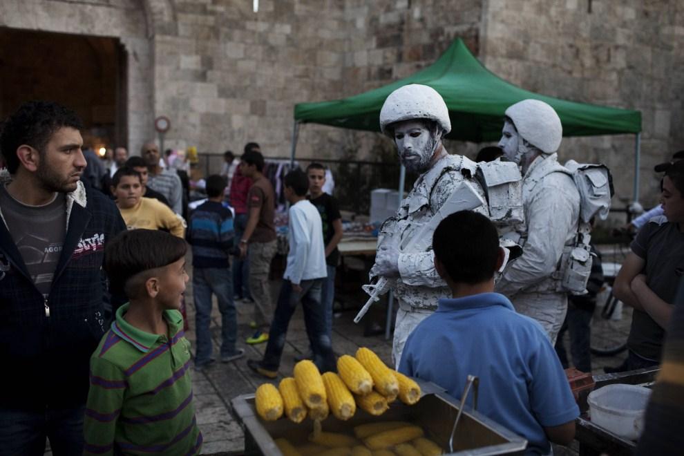 """9. IZRAEL, Jerozolima, 2 listopada 2011: Izraelscy artyści: Yuda Braun (po lewej) oraz Jonathan Peleg (po prawej) w czasie happeningu zatytułowanego """"The White Soldiers   patrol Nomansland"""". AFP PHOTO/MENAHEM KAHANA"""