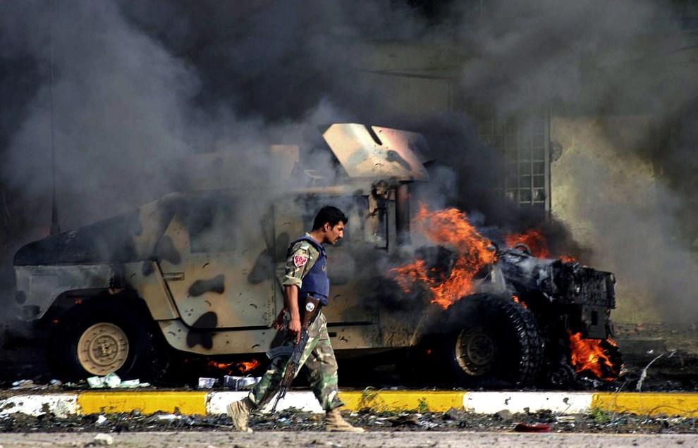 9. IRAK, Kirkuk, 19 października 2006: Irakijski policjant przechodzi obok płonącego humvee. AFP PHOTO/MARWAN IBRAHIM