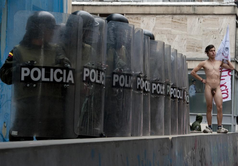 13.KOLUMBIA, Bogota, 7 września 2011: Nagi mężczyzna stoi obok policjantów podczas protestów studentów i nauczycieli w Bogocie. AFP PHOTO/Luis Acosta