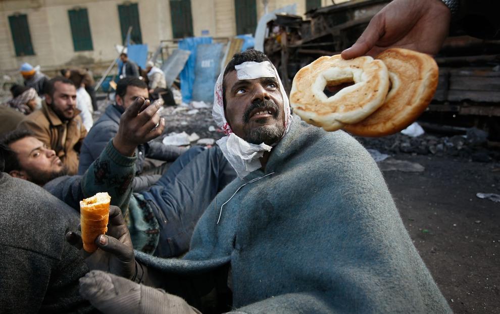 17.EGIPT, Kair, 6 lutego 2011: Ranni uczestnicy protestów otrzymują żywność. (Foto:  Chris Hondros/Getty Images)
