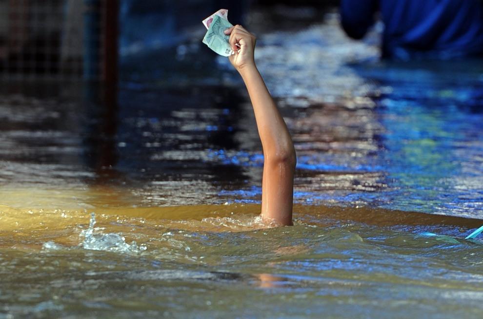 19.TAJLANDIA, Nonthaburi, 15 października 2011: Chłopiec płynący po zalanym centrum miasta stara się nie zamoczyć pieniędzy. AFP PHOTO / Pornchai KITTIWONGSAKUL