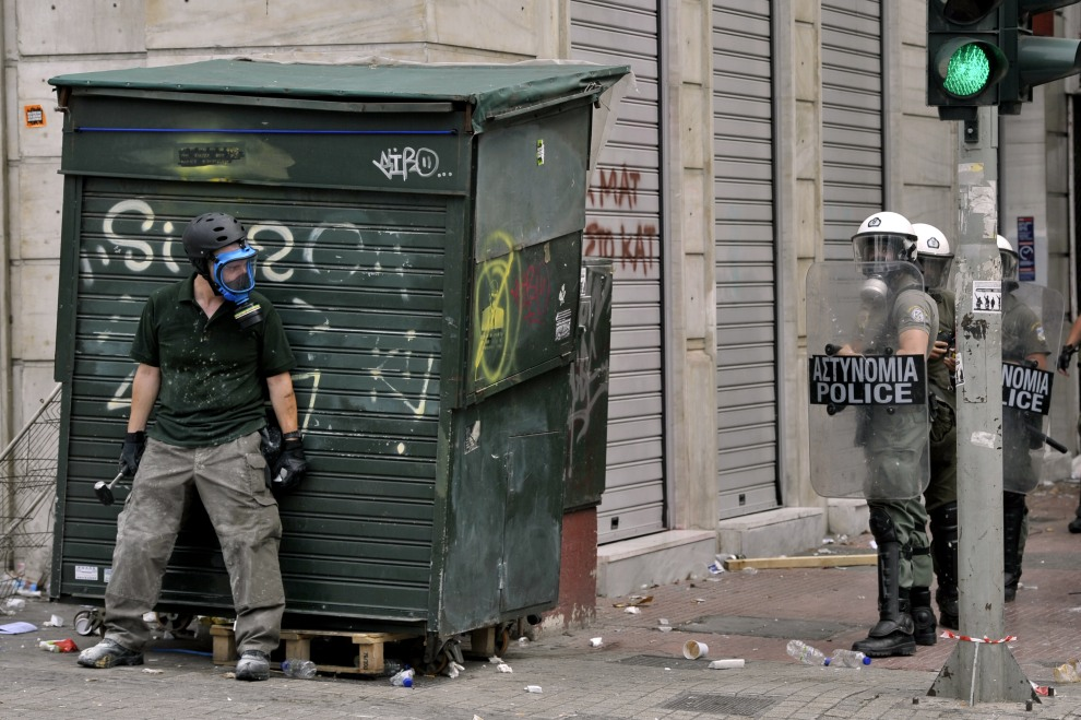 19.GREACJA, Ateny, 15 czerwca 2011: Protestujący ukrywa się przed policjantami podczas demonstracji w stolicy Grecji. AFP PHOTO / ARIS MESSINIS