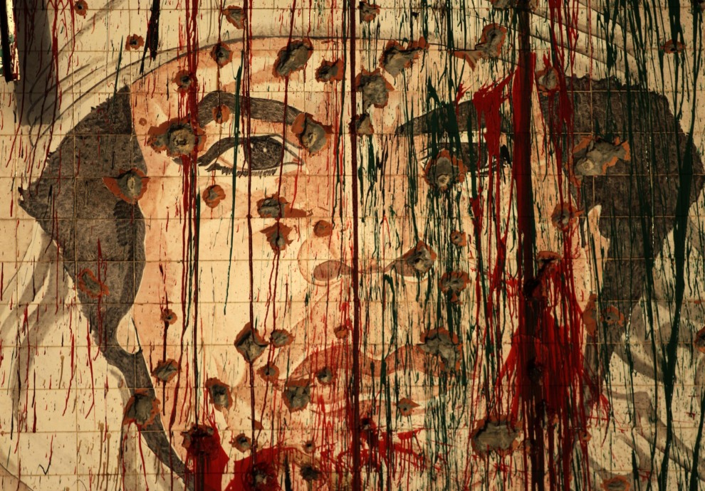 1.LIBIA, Trypolis, 1 września 2011: Ostrzelany mural z wizerunkiem Muammara Kaddafiego. AFP PHOTO/PATRICK BAZ