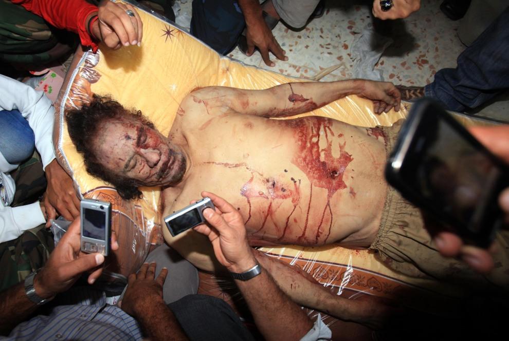 23.LIBIA, Misrata, 20 października 2011: Ciało zabitego Muammara Kaddafiego. AFP PHOTO/MAHMUD TURKIA