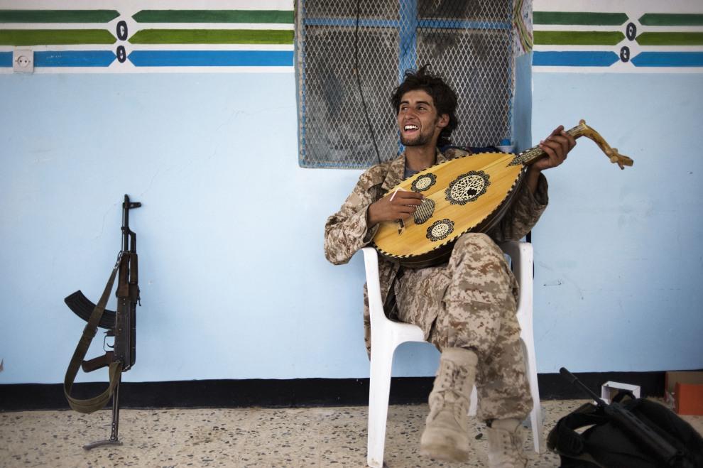 25.LIBIA, Gazaia, 28 czerwca 2011: Rebeliant grający na tradycyjnym instrumencie nazywanym oud. AFP PHOTO/ ALESSIO ROMENZI
