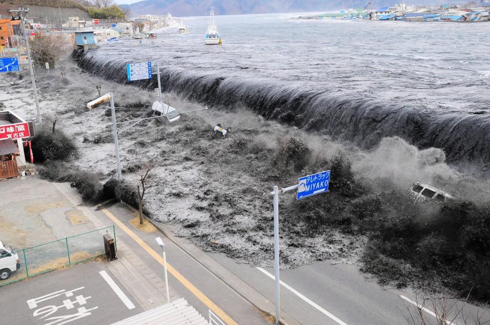 25.JAPONIA, Miyako, 15 marca 2011: Fala przelewa się przez wały na przedmieściach Miyako. EPA/Mainichi Newspaper