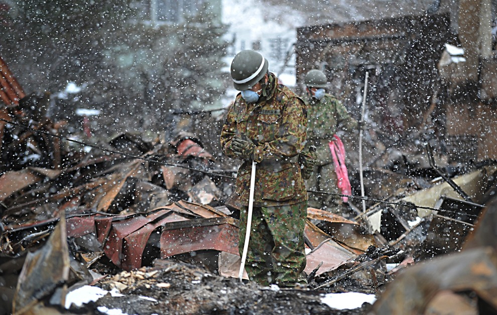 27.JAPONIA, Otsuchi, 17 marca 2011: Żołnierz modli się przed podniesienim zwłok ofiary tsunami. AFP PHOTO / Takashi NOGUCHI
