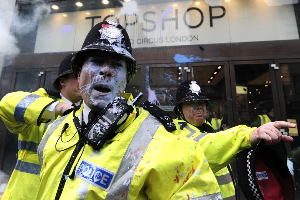 28.WIELKA BRYTNIA, Londyn, 26 marca 2011: Policjant obrzucony pojemnikiem z farbą podczas starć z przeciwnikami cięć budżetowych. AFP PHOTO / CARL COURT