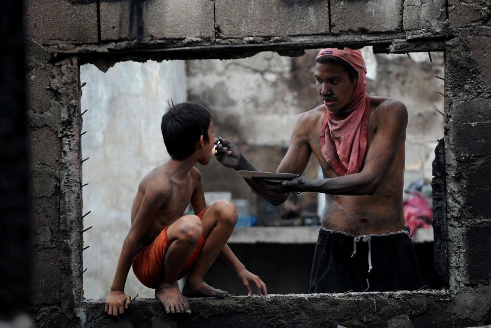 33.FILIPINY, Manila, 14 listopada 2011: Ojciec karmi syna na zgliszczach domu w jednej z dzielnic biedoty. AFP PHOTO/NOEL CELIS