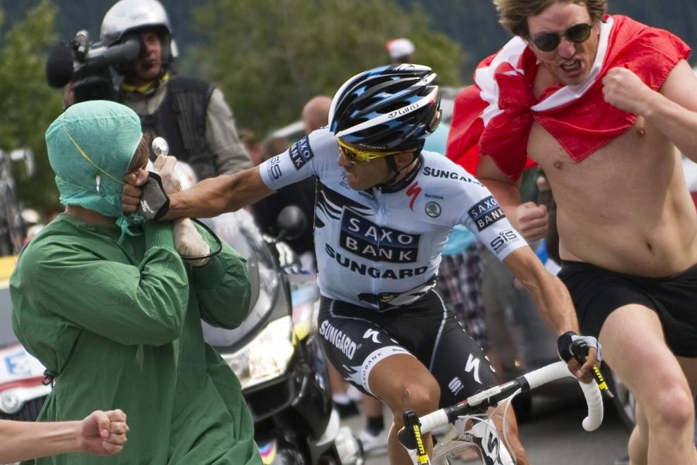 37.FRANCE, Huez, 22 licpa 2011: Alberto Contador wymierza cios biegnącemu obok i przeszkadzającemu kibicowi. AFP PHOTO POOL / LIONEL BONAVENTURE