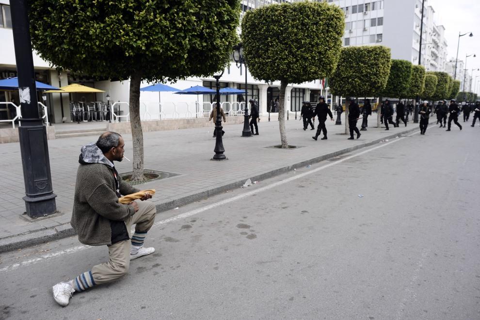 3.TUNEZJA, Tunis, 18 stycznia 2011: Mężczyzna z pieczywem na ulicy w Tunisie. AFP PHOTO / FRED DUFOUR