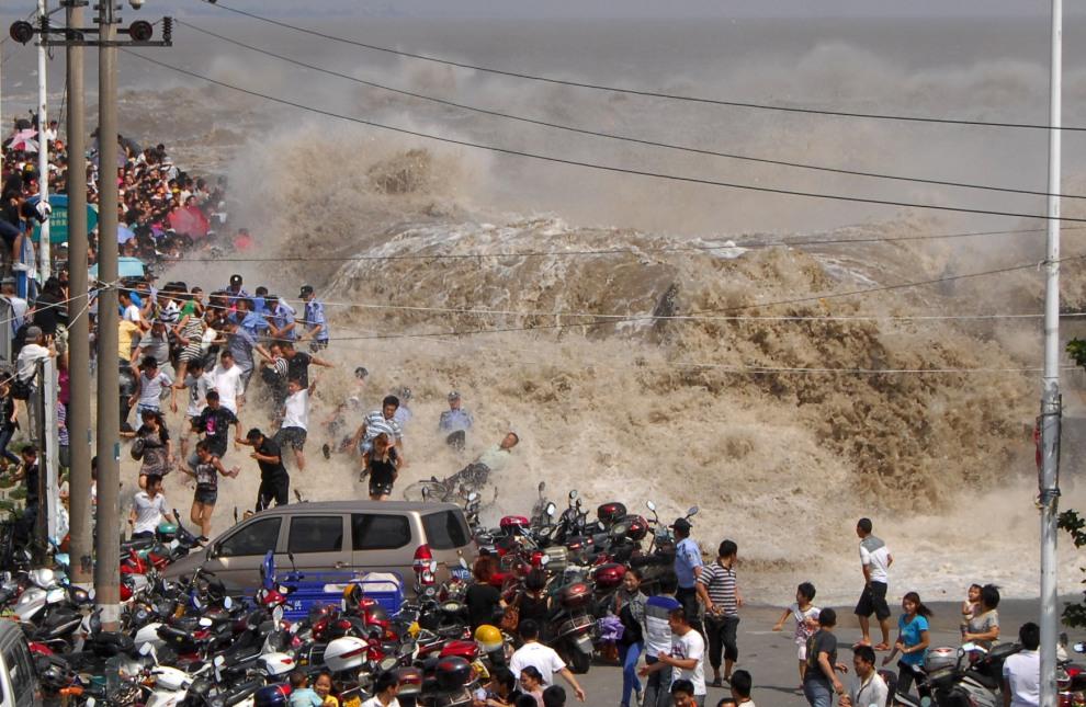 42.CHINYA, Haining, 31 sierpnia 2011: Tłum rozbiegający się pod wpływem fali przelewającej się nad zaporą na rzece Qiangtang. AFP PHOTO
