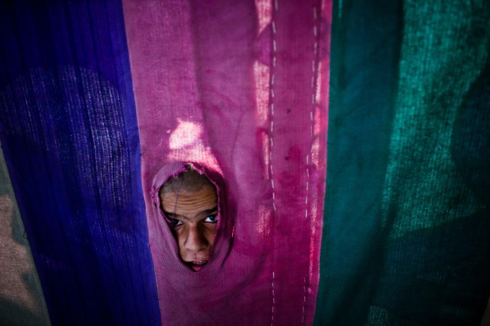 44.PAKISTAN, Islamabad, 3 sierpnia 2011: Chłopiec zagląda do namiotu z żywnościa w trakcie uroczystości związanych z ramadanem. (Foto:  Daniel Berehulak/Getty   Images)