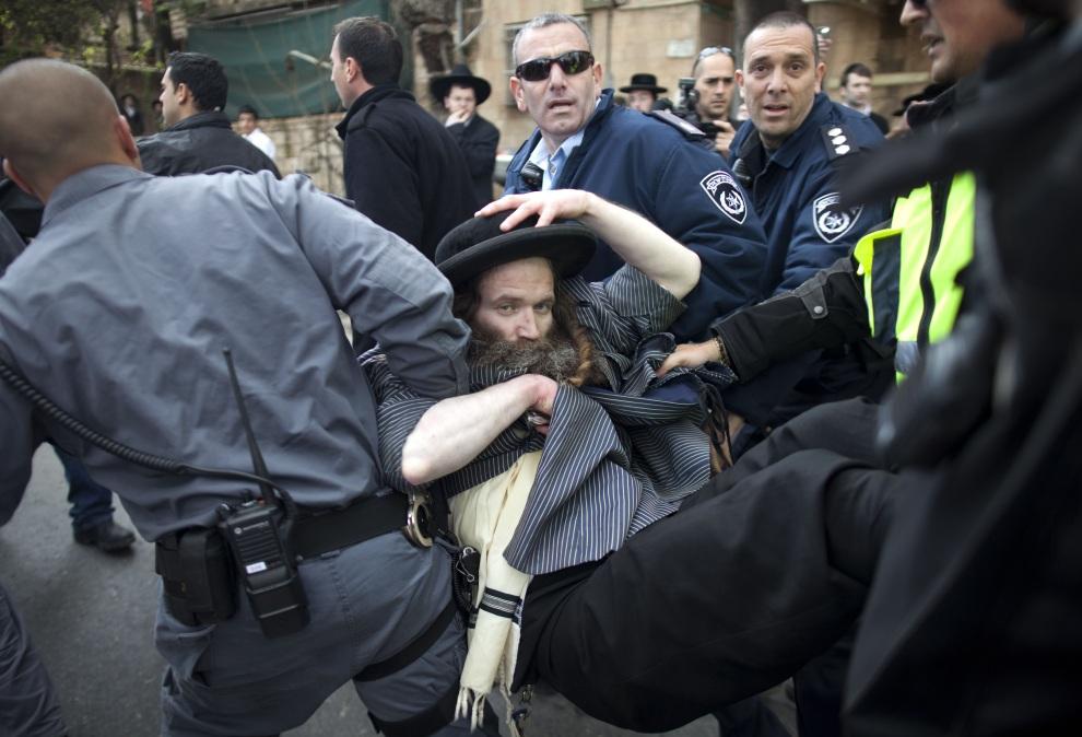 12.IZRAEL, Jerozolima, 15 stycznia 2012: Zatrzymanie uczestnika protestów w obronie aresztowanych, pod zarzutem malwersacji podatkowych, członków wspólnoty ultraortodoksyjnych Żydów. AFP PHOTO/MENAHEM KAHANA