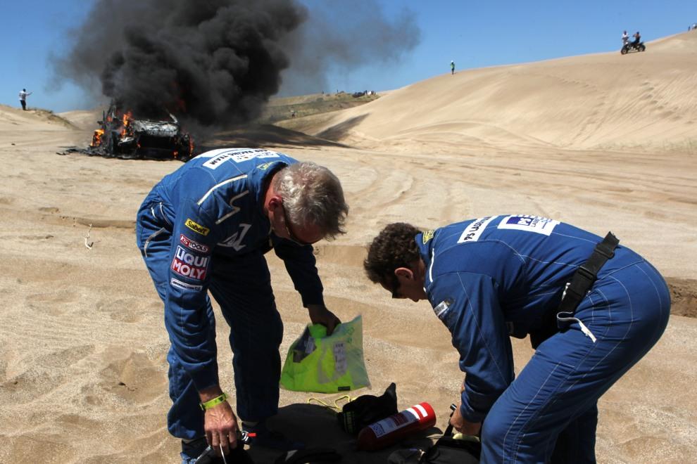 14.ARGENTYNA, Santa Rosa de la Pampa, 1 stycznia 2012: Załoga Alfie Cox i Jurgen Schroder przeglądają rzeczy wyjętę z ich płonącego Volco XC-60 Pewano. AFP   PHOTO/STR