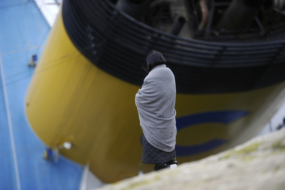 14.WŁOCHY, Isola del Giglio, 16 stycznia 2012: Pasażerka Costa Concordia na tle uszkodzonego liniowca. AFP PHOTO / FILIPPO MONTEFORTE