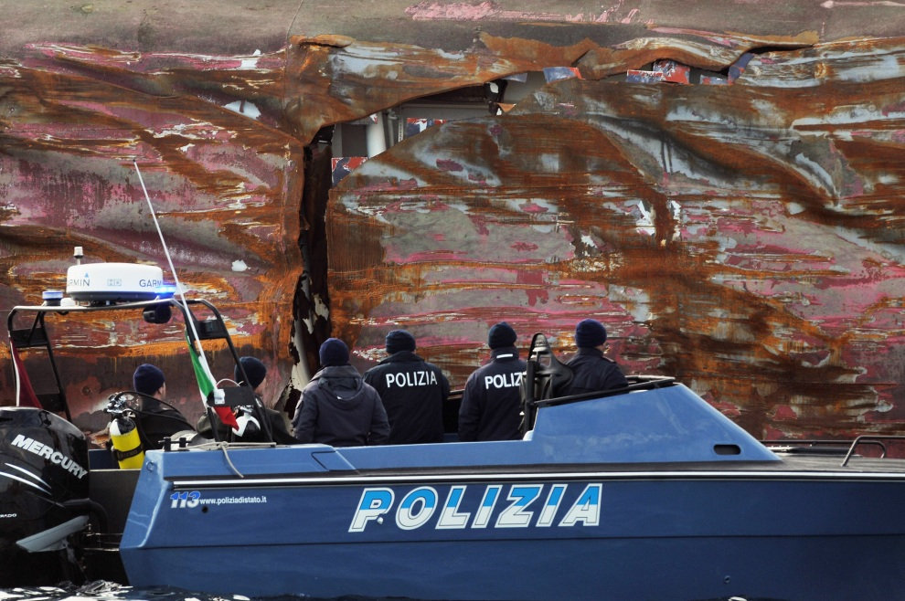 18.WŁOCHY, Isola del Giglio, 17 stycznia 2012: Łódź policyjna na tle rozdartej burty Costa Concordia. (Foto: Laura Lezza/Getty Images)