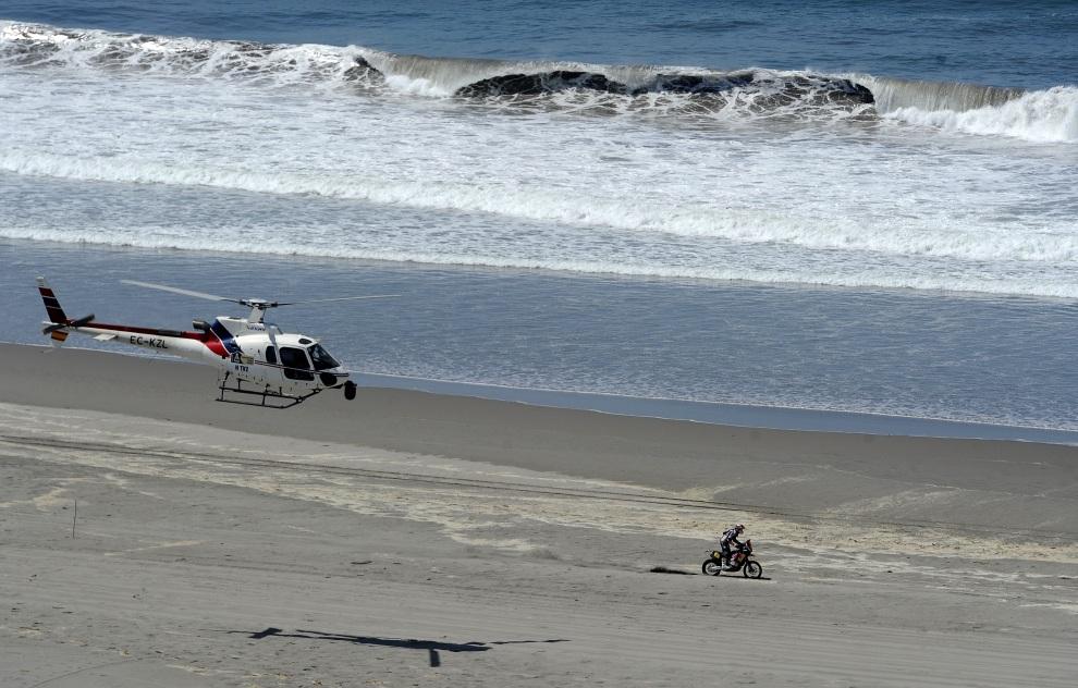 22.PERU, Nasca, 13 stycznia 2012: Helikopter przelatuje obok jadącego na KTM Cyrila Despres'a. AFP PHOTO/PHILIPPE DESMAZES