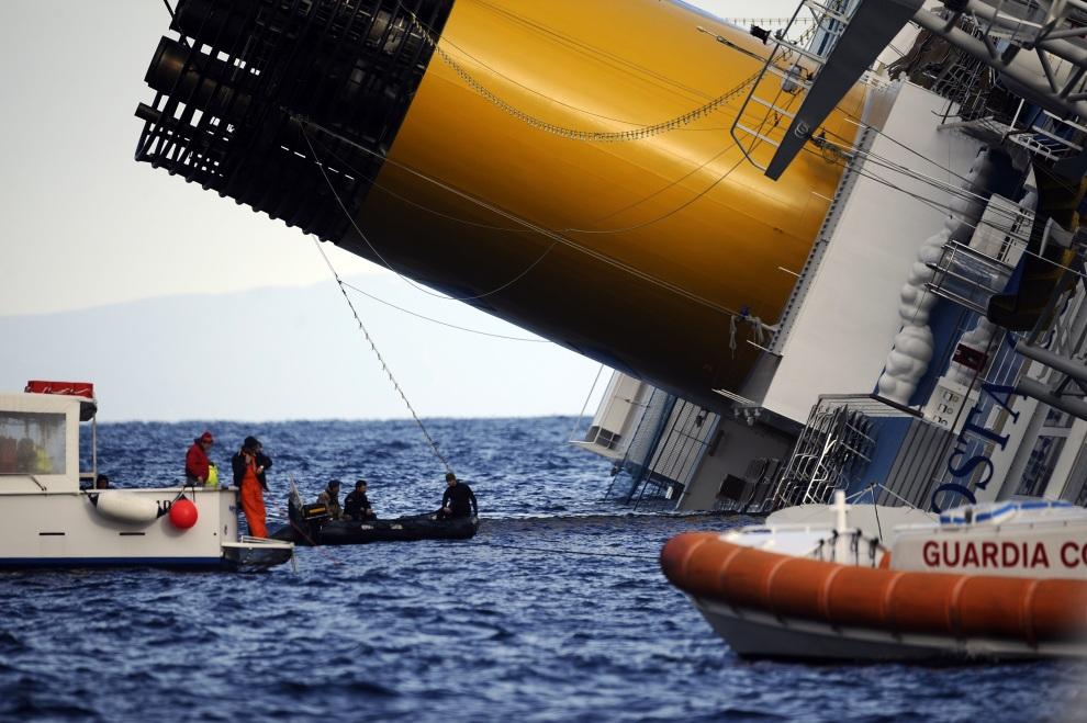 22.WŁOCHY, Isola del Giglio, 15 stycznia 2012: Łodzie patrolujące miejsce katastrofy u wejścia do portu. AFP PHOTO / FILIPPO MONTEFORTE