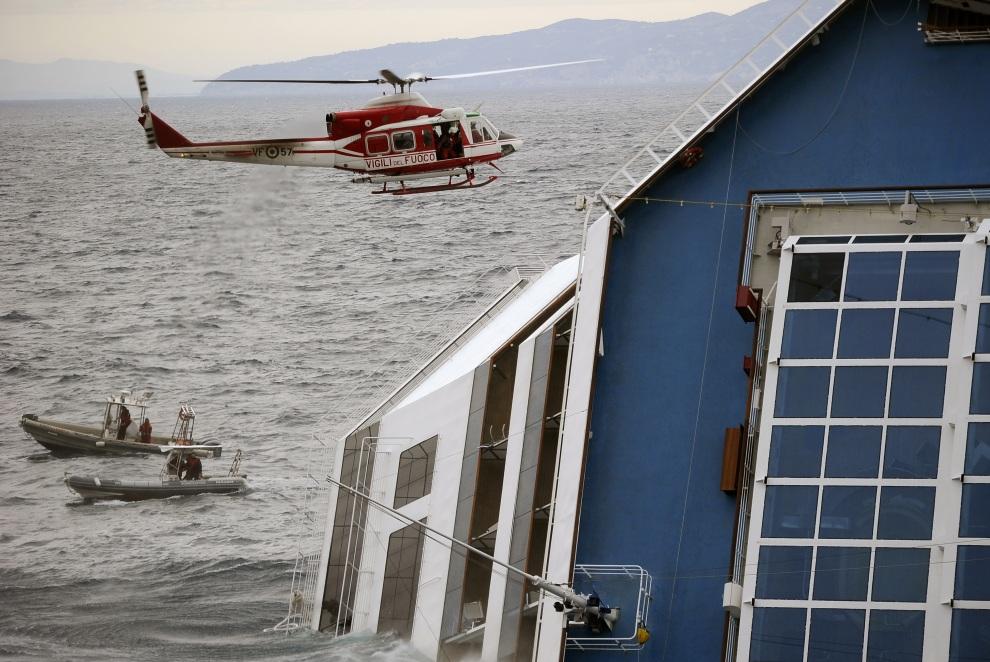 25.WŁOCHY, Isola del Giglio, 16 stycznia 2012:  Helikopter straży pożarnej zbliża się do Costa Concordia. AFP PHOTO / FILIPPO MONTEFORTE