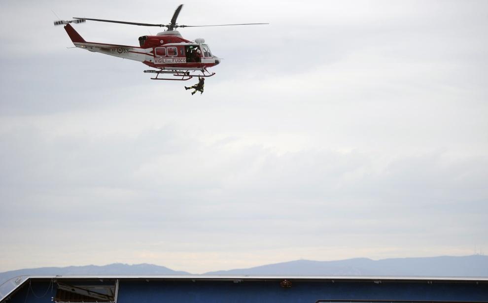26.WŁOCHY, Isola del Giglio, 13 stycznia 2012: Strażak opuszczany z helikoptera na pokład liniowca. AFP PHOTO / FILIPPO MONTEFORTE