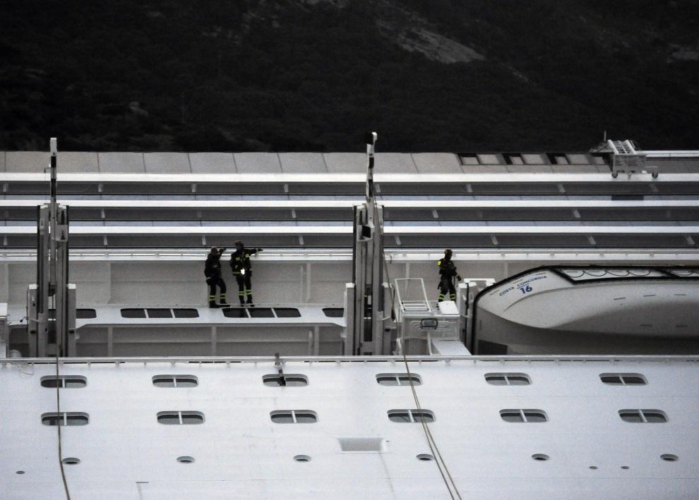 28.WŁOCHY, Isola del Giglio, 15 stycznia 2012: Strażacy na pokładzie Costa Concordia w pobliżu szalup ratunkowych. AFP PHOTO / FILIPPO MONTEFORTE