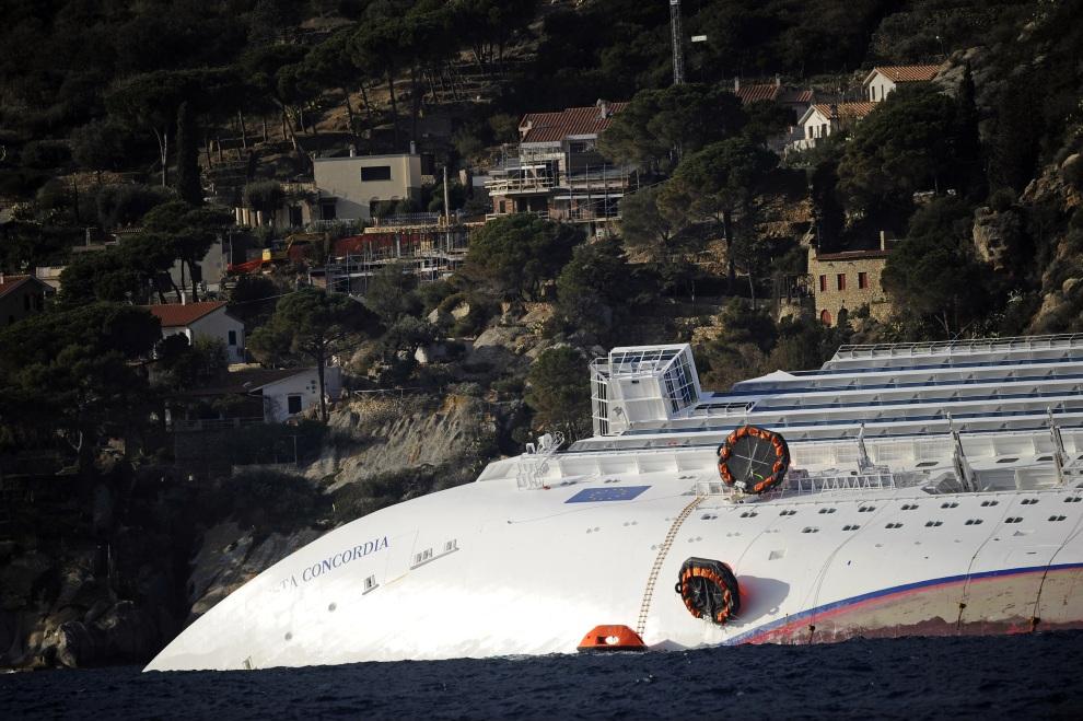 32.WŁOCHY, Isola del Giglio, 15 stycznia 2012: Uszkodzony liniowec na tle budynków na brzegu Isola del Giglio. AFP PHOTO / FILIPPO MONTEFORTE