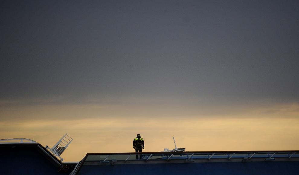 33.WŁOCHY, Isola del Giglio, 16 stycznia 2012: Strażak przygotowuje się do zjazdu z pokładu  przechylonej jednostki. AFP PHOTO / FILIPPO MONTEFORTE