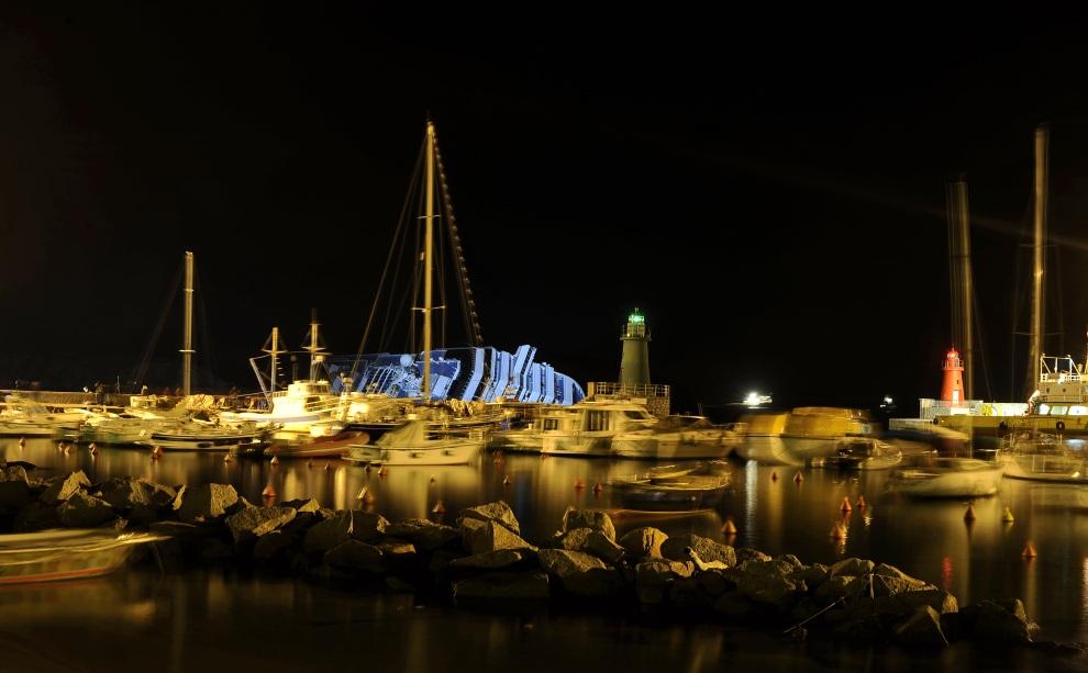 34.WŁOCHY, Isola del Giglio, 17 stycznia 2012: Port w Isola del Giglio nocą z oświetloną sylwetką  Costa Concordia. AFP PHOTO / FILIPPO MONTEFORTE