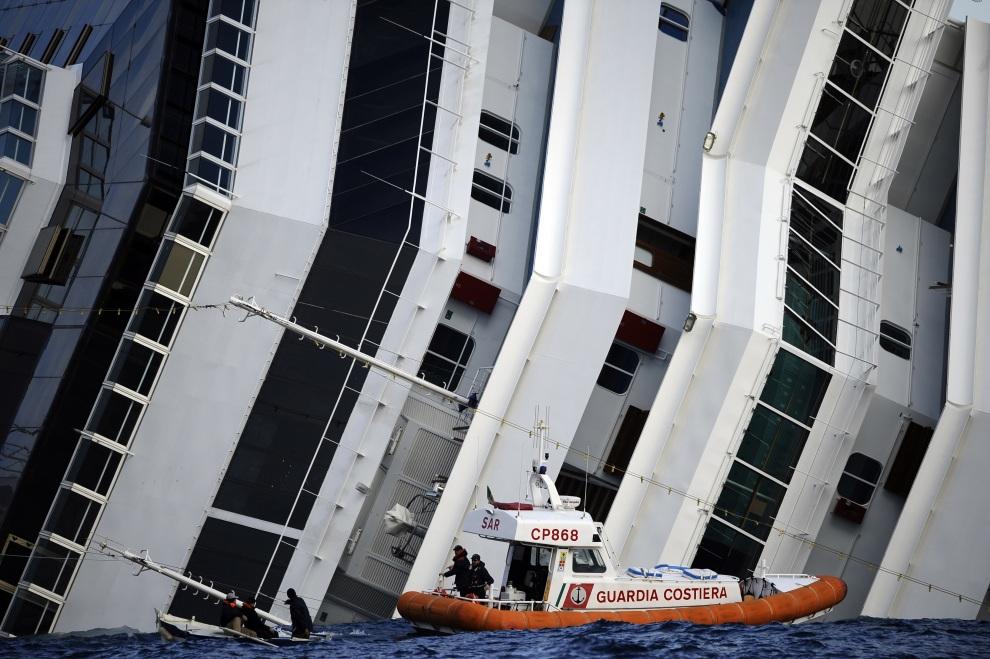 6.WŁOCHY, Isola del Giglio, 15 stycznia 2012: Łódź straży przybrzeżnej podpływa do zatopionej jednostki. AFP PHOTO / FILIPPO MONTEFORTE
