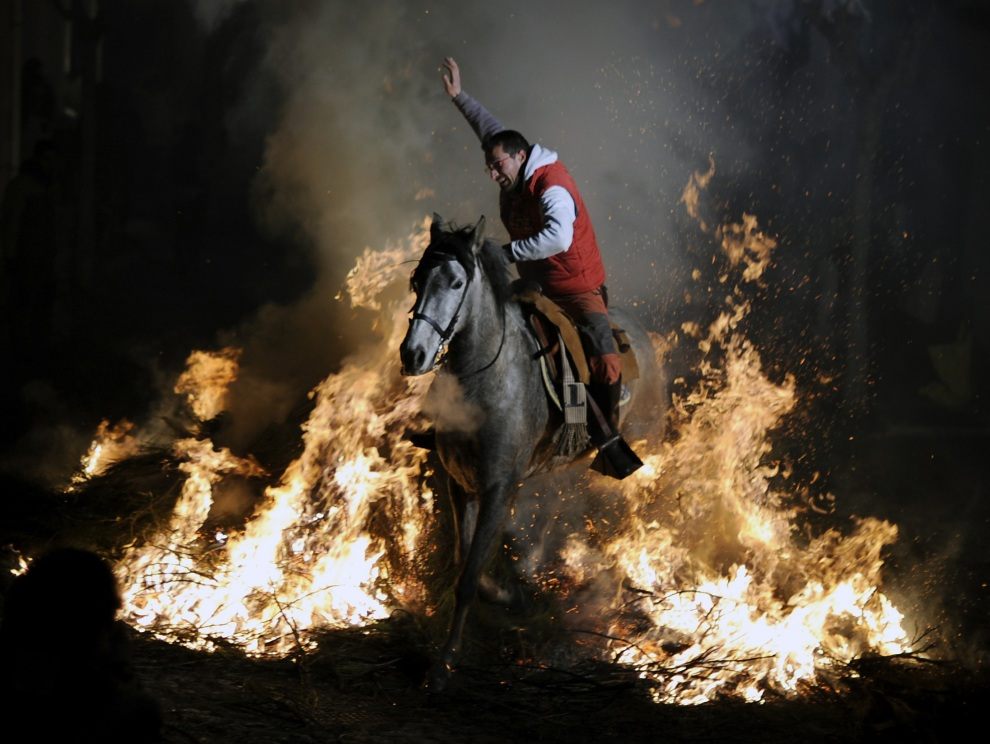 9.HISZPANIA, San Bartolome de Pinares, 16 stycznia 2012: Mężczyzna na koniu przeskakuje nad ogniskiem w trakcie uroczystości ku czci św. Antoniego. AFP PHOTO/Pedro ARMESTRE