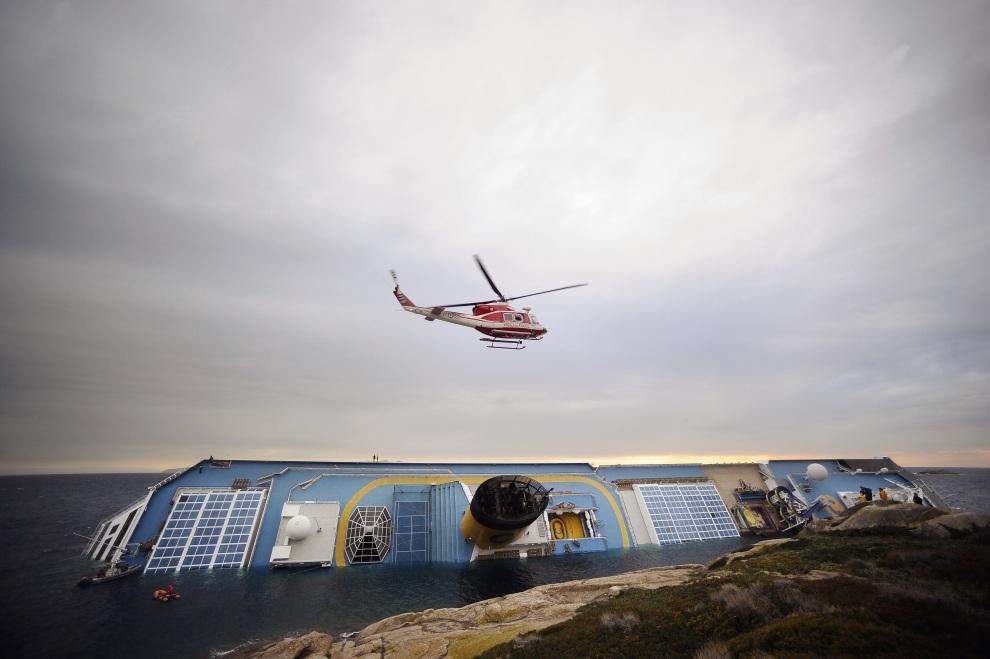8.WŁOCHY, Isola del Giglio, 16 stycznia 2012: Helikopter straży pożarnej patroluje miejsce katastrofy. AFP PHOTO / FILIPPO MONTEFORTE